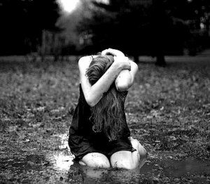 Femme agenouillée dans l'herbe boueuse1